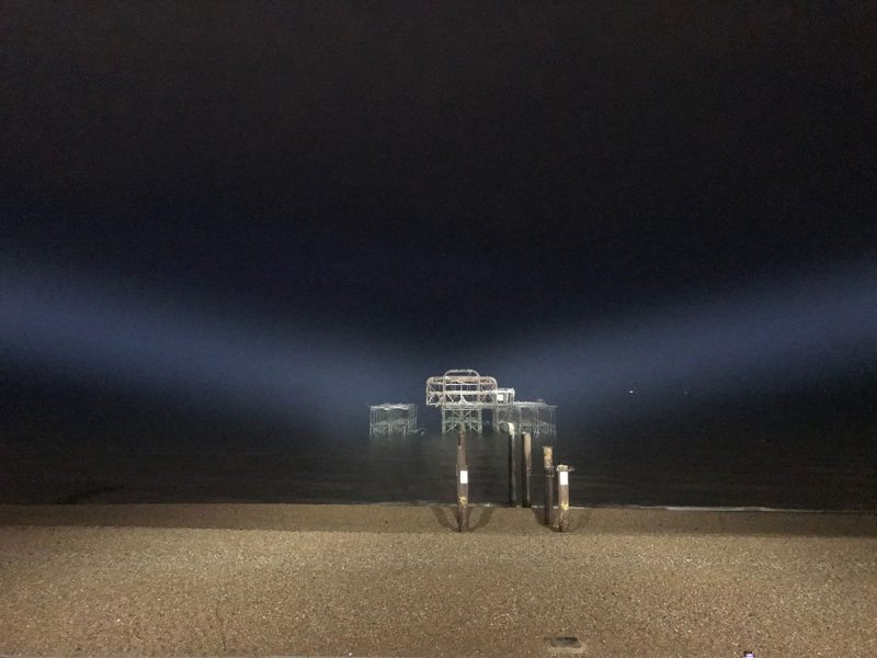 Night view of the West Pier in Brighton being illuminated by floodlights