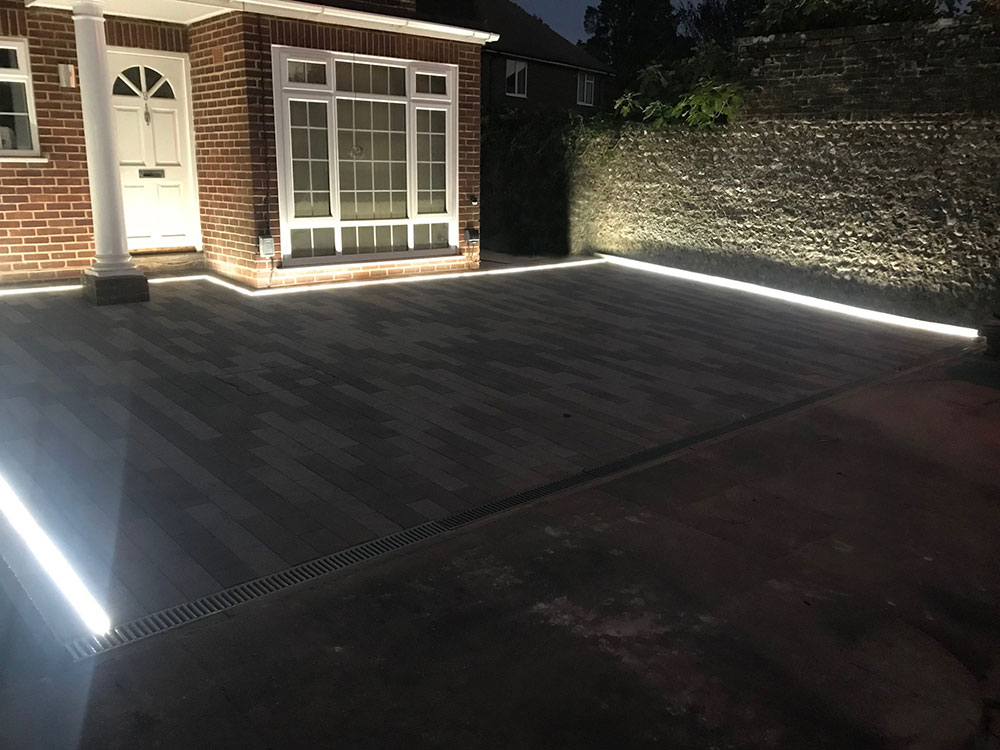 Driveway in front of a house, illuminated with sunken LED strip lighting