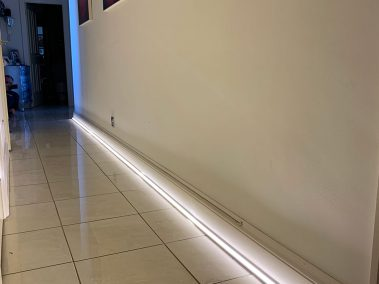 low level LED strip light installed in a hallway