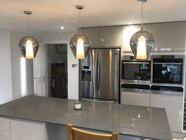 three hanging lights over a kitchen island