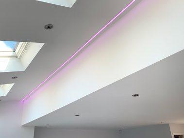 pink LED lighting strip illuminating a kitchen ceiling