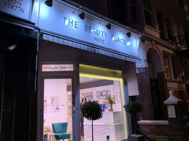 Illuminated shop front of the Beauty Place in Hove